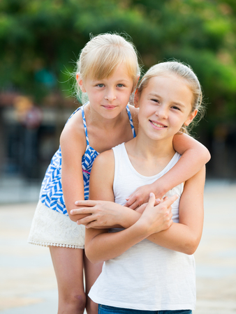 5s: Two smiling little girls embracing each other in summer park