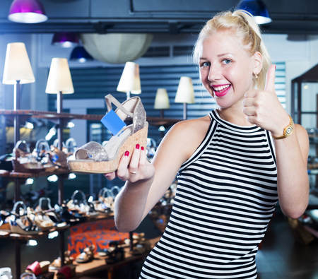 cheerful young female customer showing desired shoe in fashion  department Stock Photo