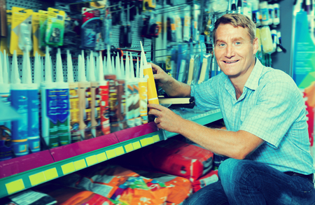 sealant: Adult man customer picking sealing component in household shop Stock Photo