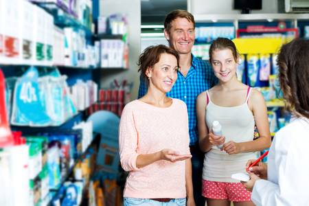Portrait of happy parents with daughter teenager talking to pharmacist in drug store Stock Photo