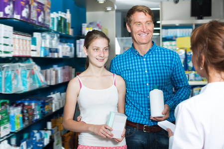 Adult father with teenager daughter consulting druggist in pharmacy Stock Photo