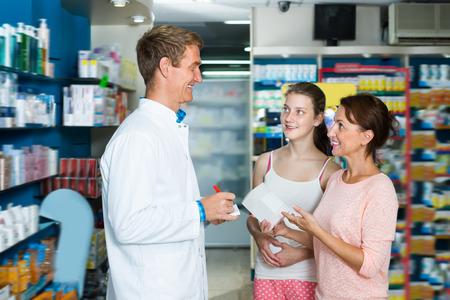 Happy pharmacist wearing white coat helping customers in drug store