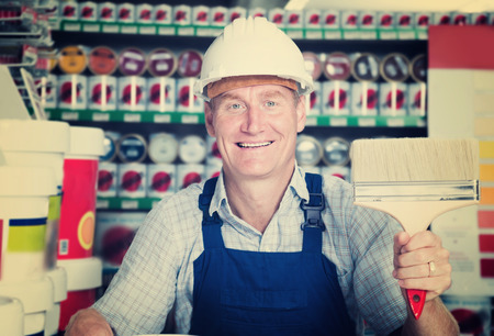 housewares: Glad workman in hardhat buying painting roller in household store