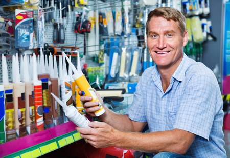 Portrait of  cheerful smiling male customer selecting sealant bottle in housewares department