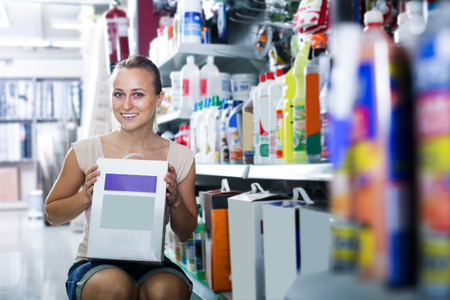 housewares: cheerful young woman customer holding box with dry filler in housewares hypermarket