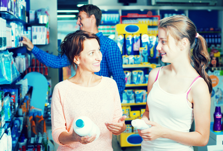 Cheerful mother with teenager daughter choosing healthcare products in pharmacy