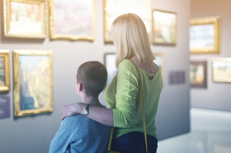 happy american mother and son looking at paintings in halls of museum