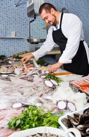 fish vendor: Smiling friendly positive seller in black apron shows fish counter