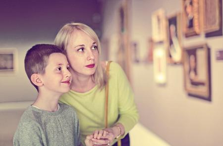 박물관의 복도에서 회화에 관해서 행복한 명랑한 어머니와 아들을 웃어 라.