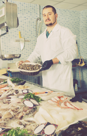 supermarket: Glad  positive seller holds basket of small mussels standing near a counter with seafood