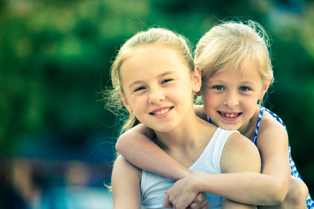5s: Two small happy sisters fun spending time together outdoors