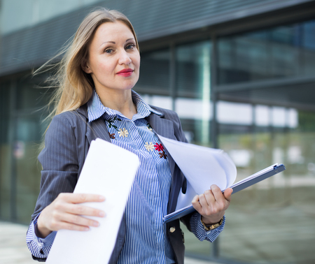 Employee woman in suit standing with folder of documents at the city Stock Photo