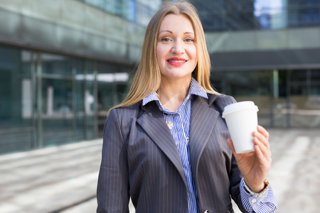 Portrait of cheerful female with coffee at the modern street