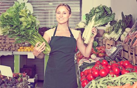 supermarket: Glad young female seller wearing apron holding fresh celery and mangold on market Stock Photo