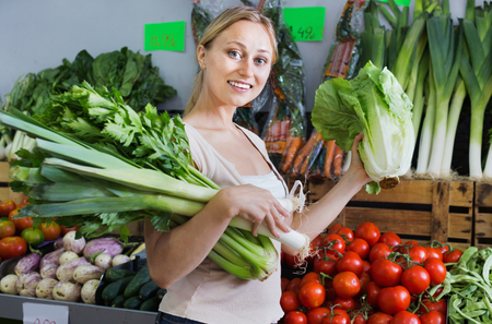 supermarket: Portrait of young positive cheerful woman shopping fresh green celery, leek and lettuce in shop Stock Photo