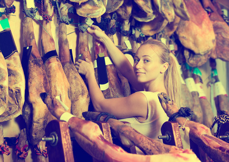 supermarket: Attractive woman picking delicious prosciutto meat on market Stock Photo