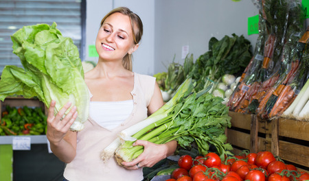 smiling  woman customer buying fresh green celery and lettuce in store