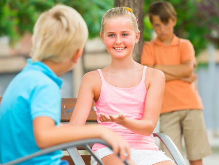argue kid: Kids are talking in the distance from their offended friend. Stock Photo