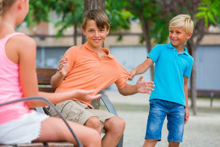 Meisje is aan het praten met een jongen en zijn jongere broer is jaloers op het park. Stockfoto