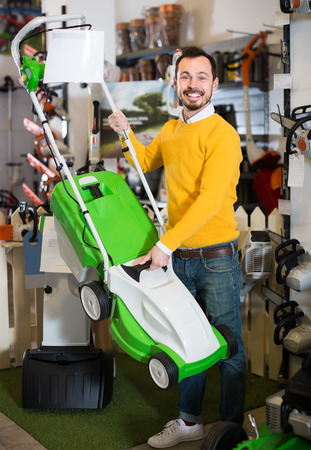 guy deciding on best lawnmower from assortment in garden equipment shop Stock Photo