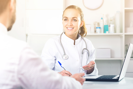 hospital patient: Smiling woman doctor consulting client  in hospital Stock Photo
