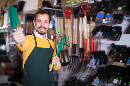 hardware: friendly male seller showing assortment ?f equipment in garden equipment shop