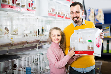 boasting: positive european father and daughter enjoying their purchase of canary bird in pet shop