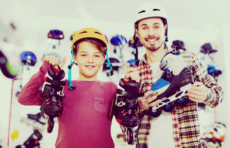 boasting: Young glad cheerful  father and son showing roller-skates they bought in sports store
