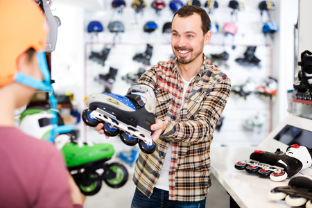 Smiling male seller demonstrating roller-skates to boy customer in sports store