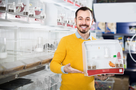 Young positive man enjoying his purchase of canary bird in pet shop Stock Photo