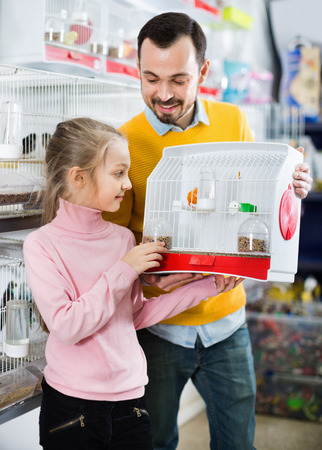 Smiling happy cheerful positive father and daughter boasting their purchase of canary bird in pet shop