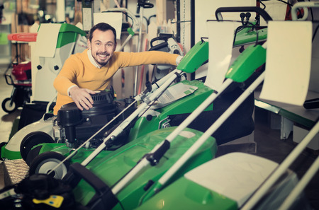 hardware: cheerful guy deciding on best lawnmower from assortment in garden equipment shop Stock Photo