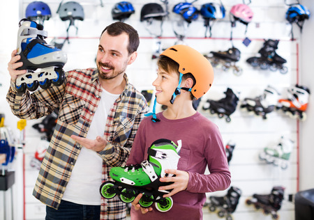 positive spanish male shop assistant helping boy to choose roller-skates in sports store Stock Photo