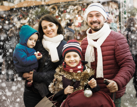 Portrait of happy family with two children posing outdoors in winter. Focus on woman