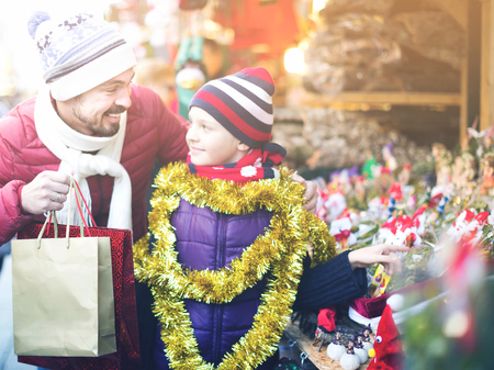 overspending: Happy father with small daughter buying decorations for Xmas in Christmas market. Focus on man