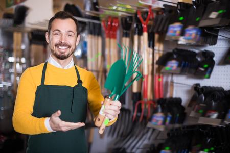 Handsome male seller demonstrating assortment in garden equipment shop Reklamní fotografie
