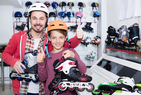 boasting: Cheerful father and son boasting purchased roller-skates in sports store