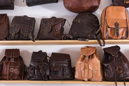 Handmade leather backpacks and bags on shelf in european shop