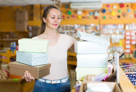 Ordinary girl with gift boxes in her hands chooses accessories for gift in store Stock Photo