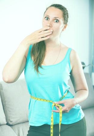 Young woman having problems with weight gain at home Stock Photo