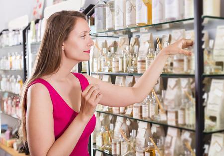 choise: Happy woman take a choise fresh perfume in perfume supermarket