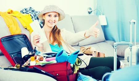 Young cheerful woman packing luggage for holidays at home