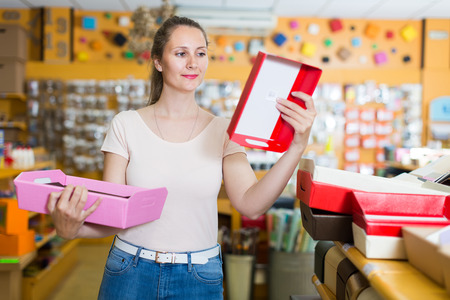 pasteboard: female customer selects boxes and containers for gifts in the supermarket Stock Photo