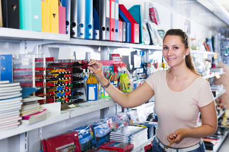 Emotional female buying different products in stationery shop