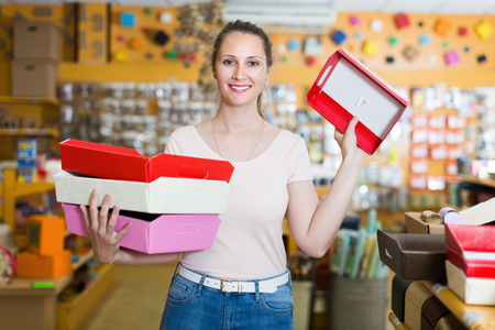 Young female with other multi colored gift boxes smiling at shop