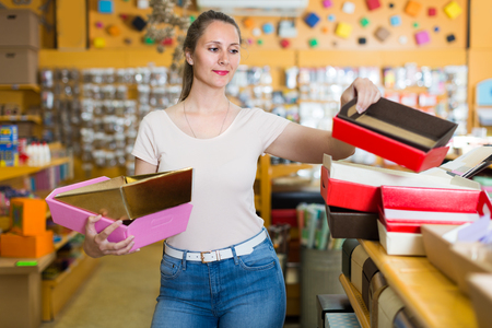 Girl is choosing red or pink palettes for trifle in store. Stock Photo