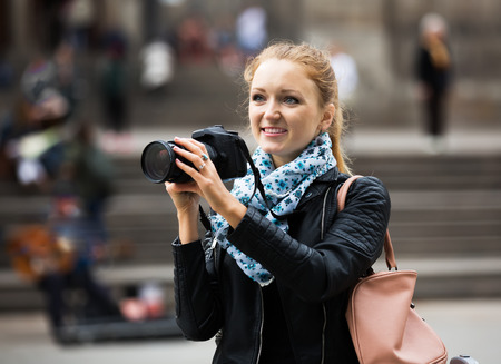 25s: Portrait of young woman traveller with photo camera outdoors Stock Photo
