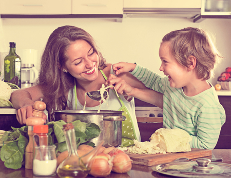 Happy woman with little daughter cooking with vegetables at home kitchen photo