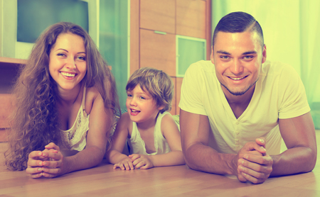 Smiling young parents with four-year child in home interior. Focus on woman photo