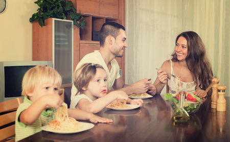 Happy young family of four eating with spaghetti at table photo